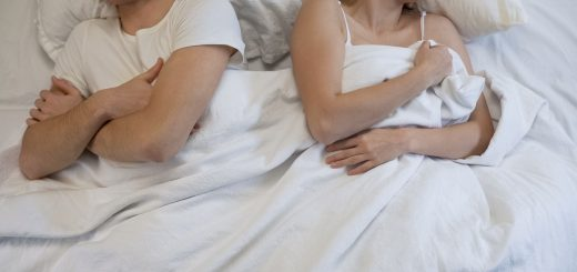 Young wife and husband fighting in bed, feeling uncomfortable on sleep place